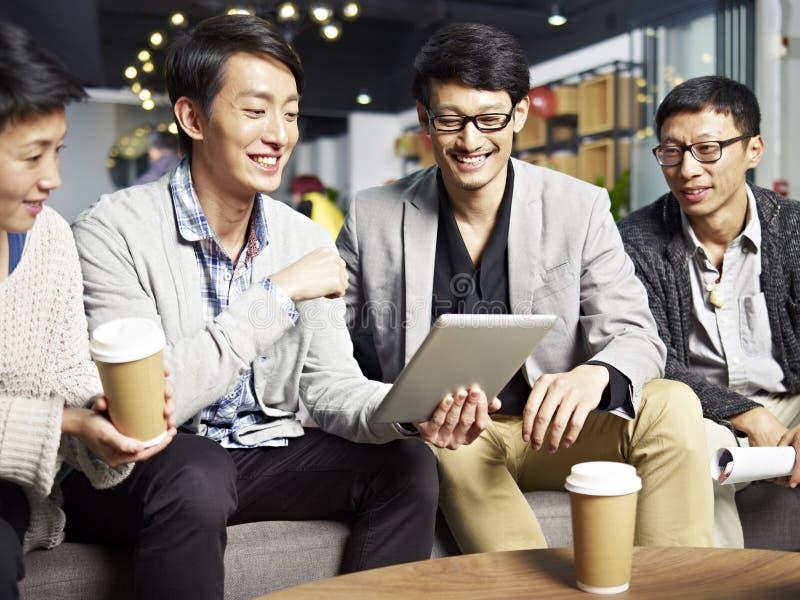 Gens d'affaires asiatiques à l'aide du comprimé dans le bureau photos stock