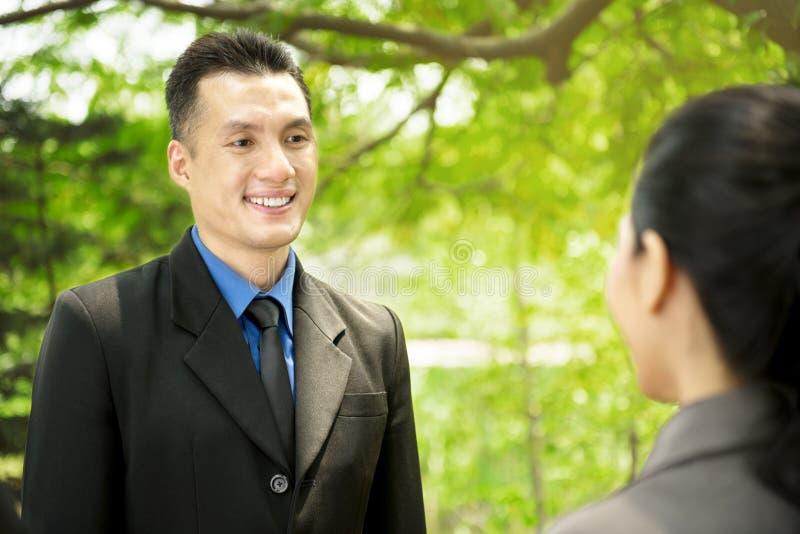 Gens d'affaires asiatiques discutant le plan de travail à extérieur photographie stock libre de droits