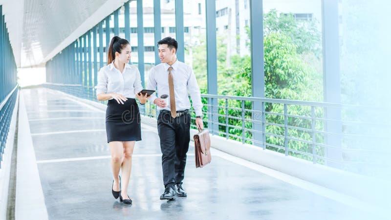 Gens d'affaires asiatiques marchant et parlant du travail dehors de images stock