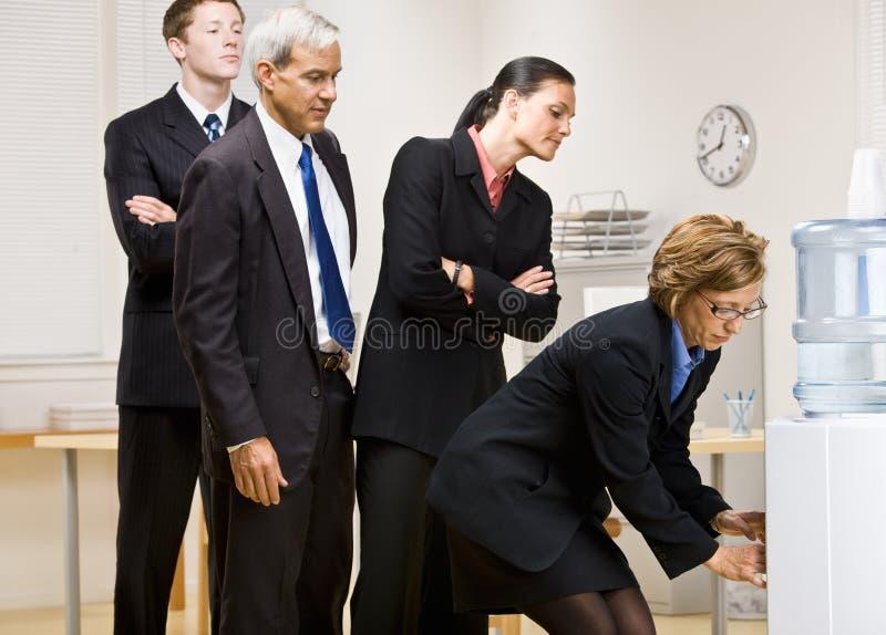 Gens d'affaires attendant le virage au refroidisseur d'eau images stock