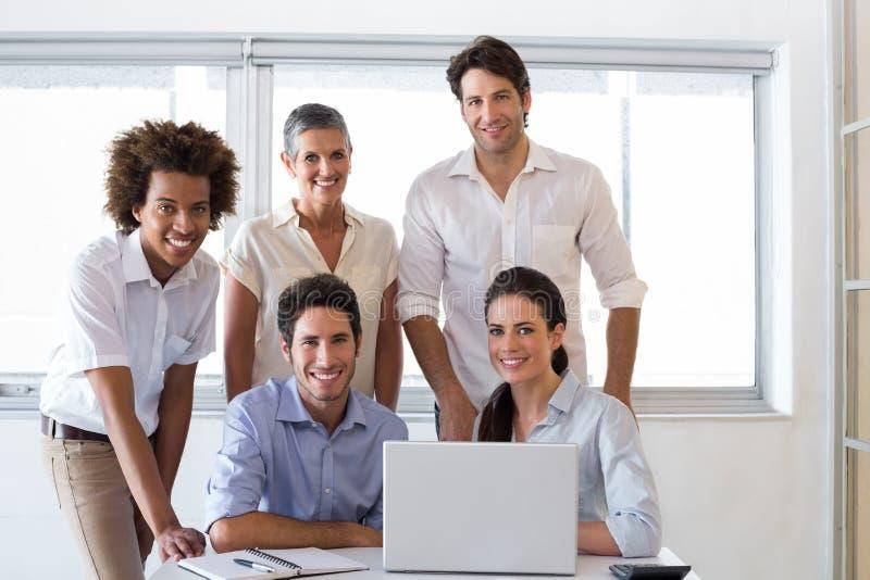 Gens d'affaires attirants souriant dans le lieu de travail photos libres de droits