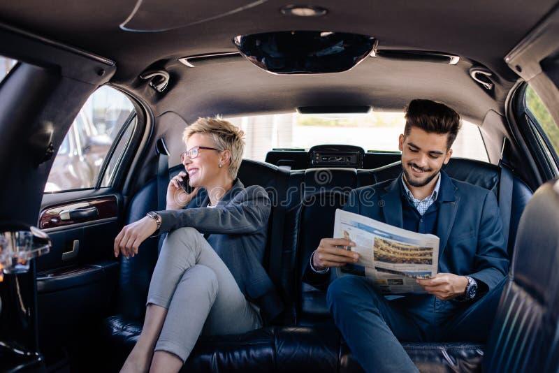 Gens d'affaires au siège arrière de la limousine photo stock