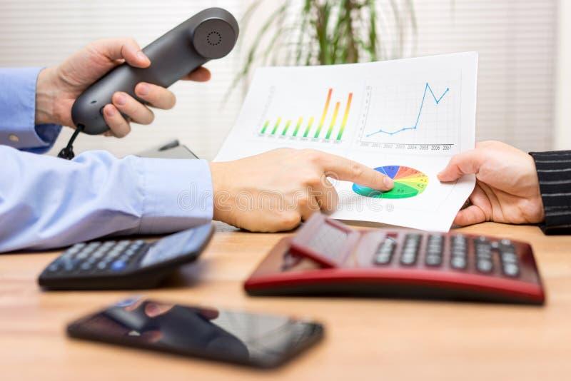 Gens d'affaires ayant une discussion au sujet du rapport financier NAD c image stock