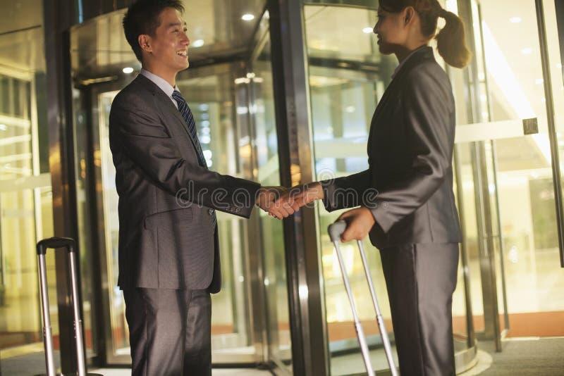 Gens d'affaires de poignée de main en dehors de du bureau photo libre de droits
