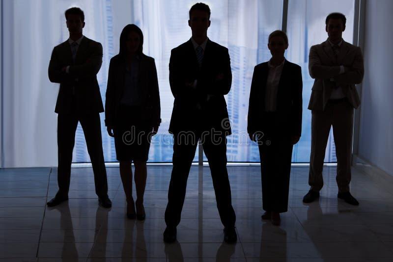 Gens d'affaires de silhouette se tenant dans le bureau photos libres de droits