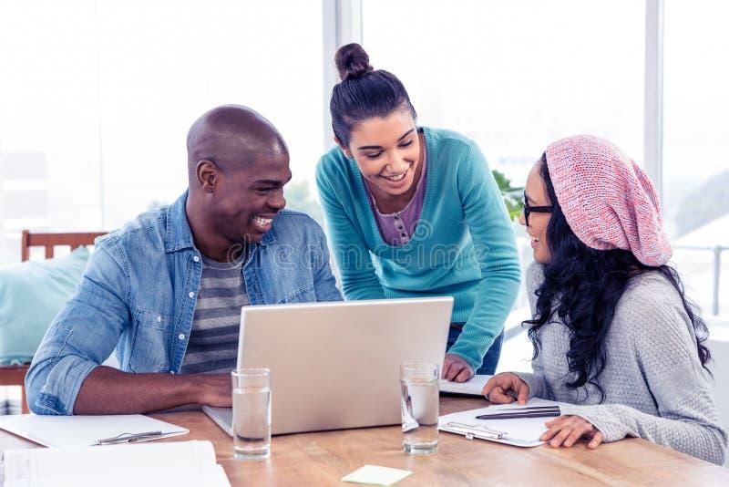 Gens d'affaires discutant au-dessus de l'ordinateur portable dans le bureau images stock