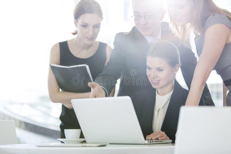 Gens d'affaires discutant au-dessus de l'ordinateur portable dans le cafétéria de bureau photographie stock