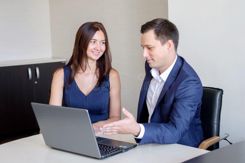 Gens d'affaires discutant des idées lors de la réunion utilisant l'ordinateur portable dans le bureau photo libre de droits