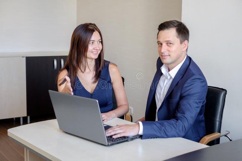 Gens d'affaires discutant des idées lors de la réunion utilisant l'ordinateur portable dans le bureau photos libres de droits