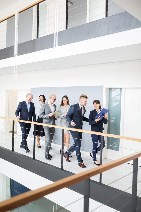 Gens d'affaires discutant tout en marchant sur le couloir dans le bureau images libres de droits