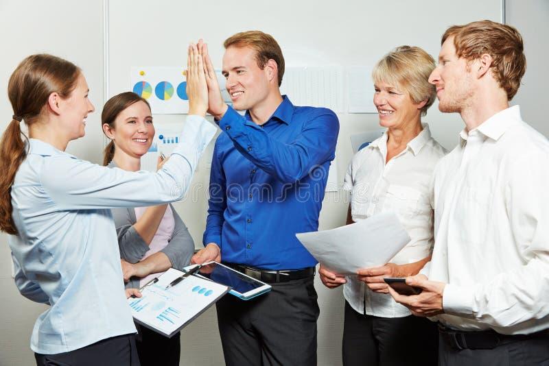 Gens d'affaires donnant la haute cinq lors d'une réunion photo libre de droits