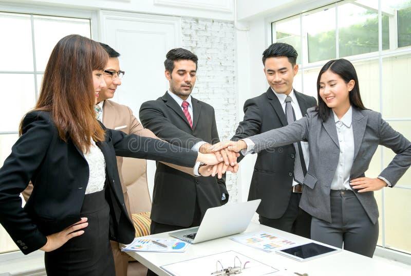 gens d'affaires empilant des mains dans le lieu de réunion image libre de droits
