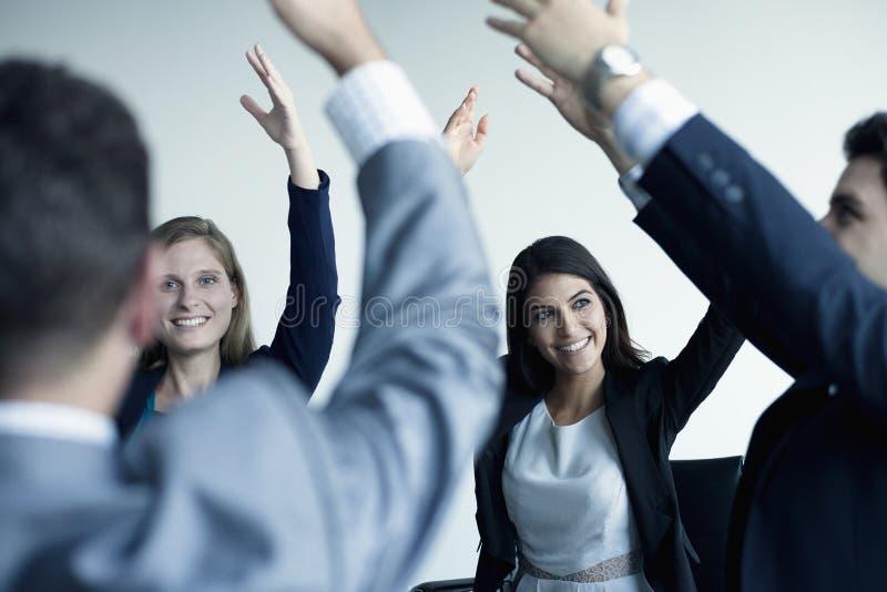 Gens d'affaires encourageant avec des bras dans le ciel photographie stock libre de droits