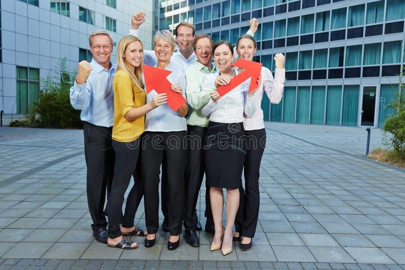 Gens d'affaires encourageants d'équipe avec des flèches image libre de droits