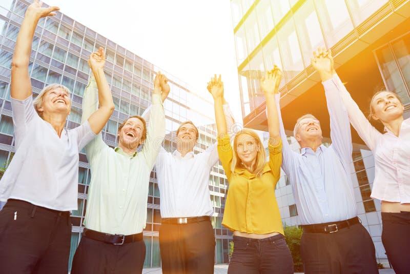 Gens d'affaires encourageants soulevant des bras image stock