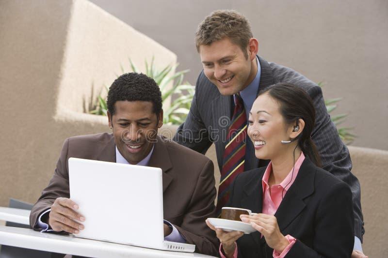 Gens d'affaires ethniques multi souriant tout en regardant l'ordinateur portable images stock