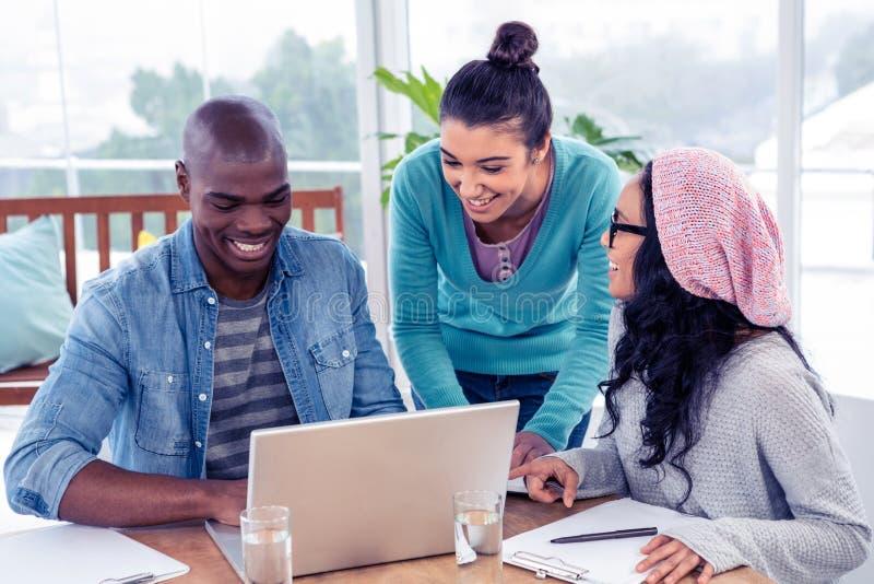 Gens d'affaires gais discutant au-dessus de l'ordinateur portable images stock