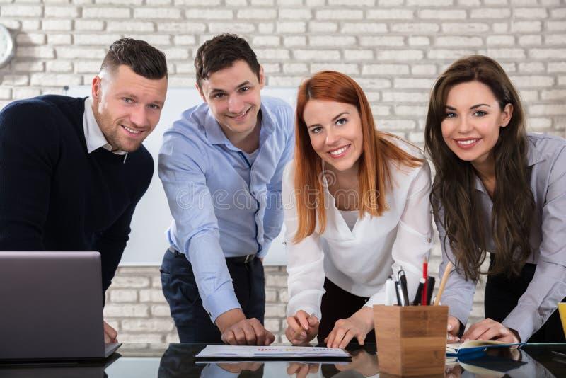 Gens d'affaires heureux effectuant le travail sur le lieu de travail photo libre de droits