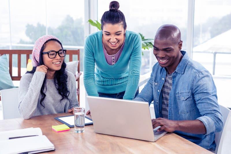 Gens d'affaires heureux regardant l'ordinateur portable photographie stock libre de droits