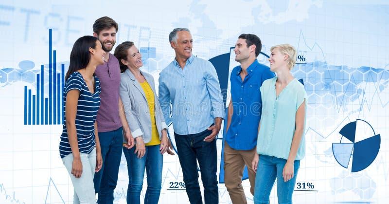 Gens d'affaires heureux se tenant contre des graphiques photographie stock libre de droits