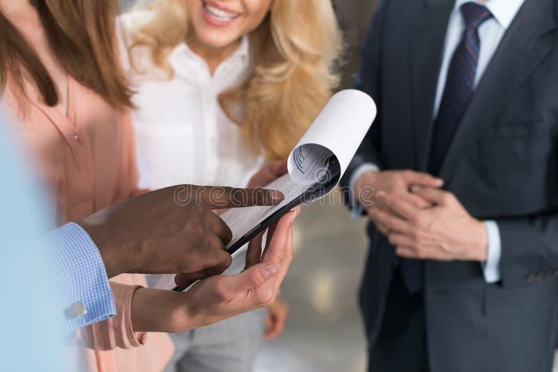 Gens d'affaires lisant des documents, associés discutant le fichier papier de contrat dans le bureau moderne avant la signature image stock