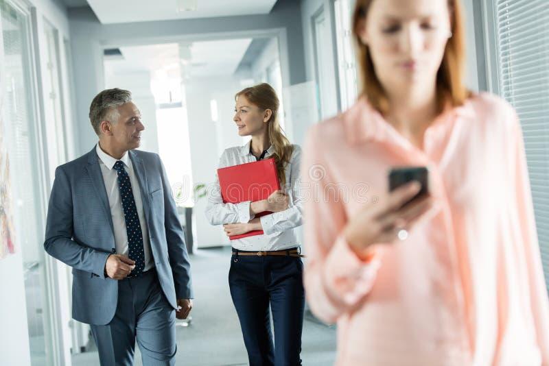 Gens d'affaires marchant dans le couloir avec le collègue féminin à l'aide du téléphone portable dans le premier plan au bureau photographie stock libre de droits