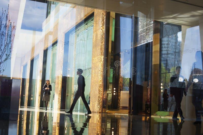 Gens d'affaires marchant par le lobby d'un immeuble de bureaux de l'autre côté d'un mur de verre photographie stock