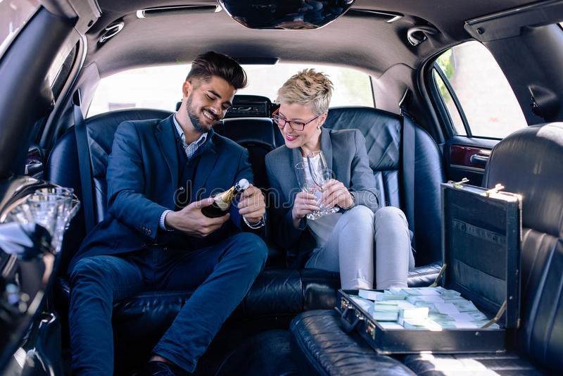 Gens d'affaires ouvrant le champagne dans la limousine images stock