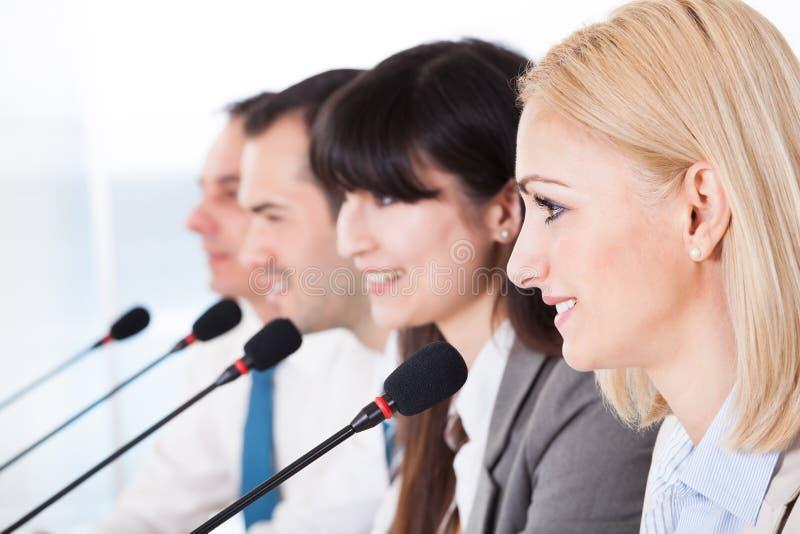 Gens d'affaires parlant dans le microphone images stock