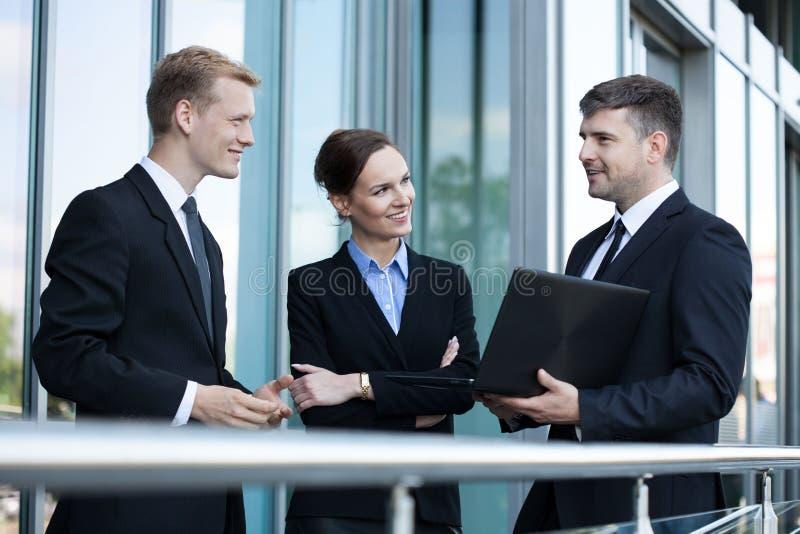 Gens d'affaires parlant devant l'immeuble de bureaux photo stock
