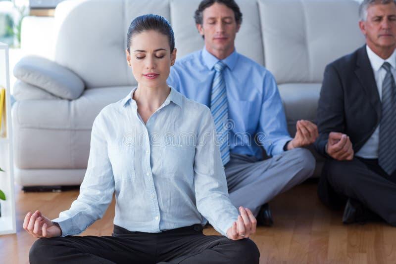 Gens d'affaires pratiquant le yoga photo stock