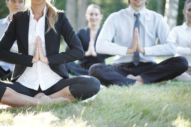 Gens d'affaires pratiquant le yoga image stock
