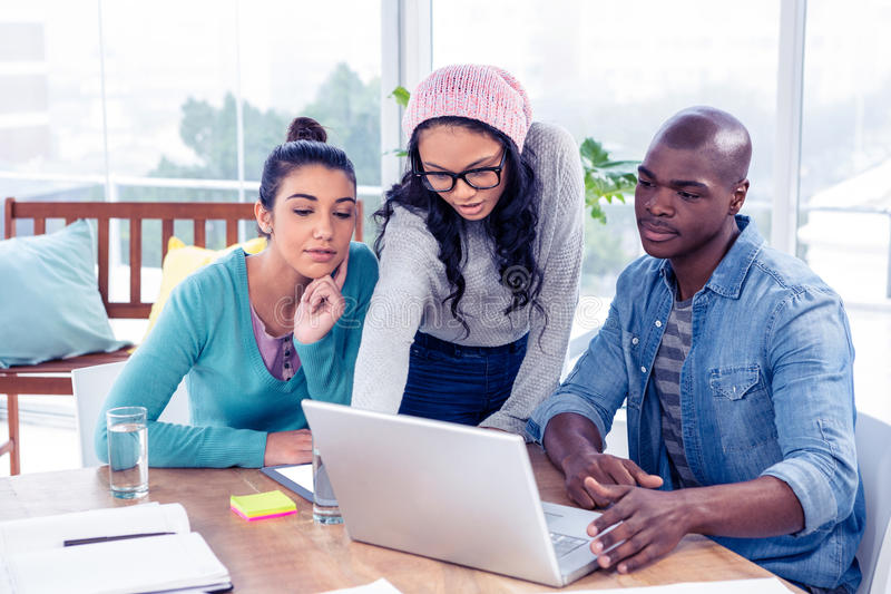 Gens d'affaires regardant l'ordinateur portable sur le bureau photo stock