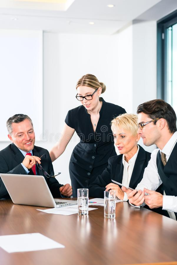 Gens d'affaires regardant l'ordinateur portatif photographie stock libre de droits