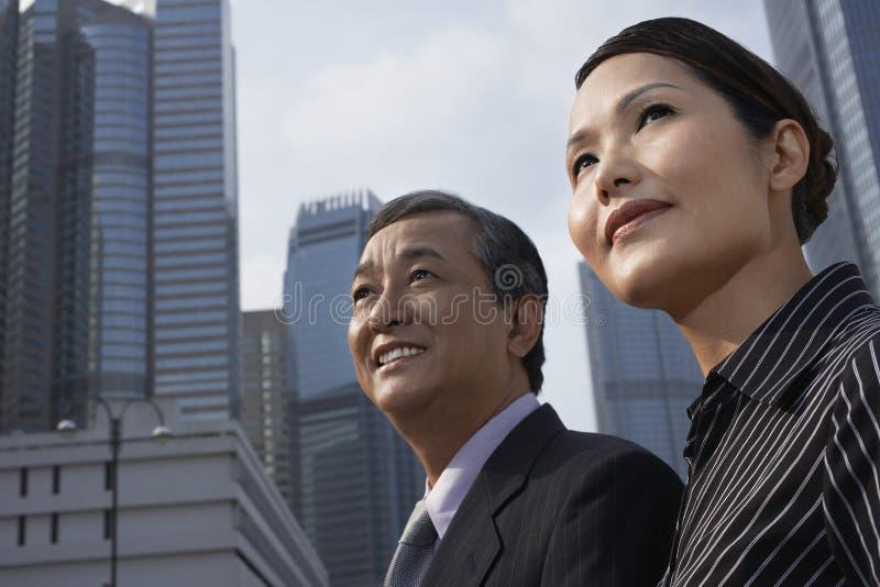 Gens d'affaires regardant loin contre des bâtiments image stock