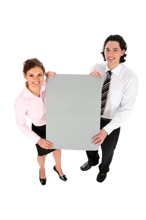 Gens d'affaires retenant le panneau blanc d'affiche images stock