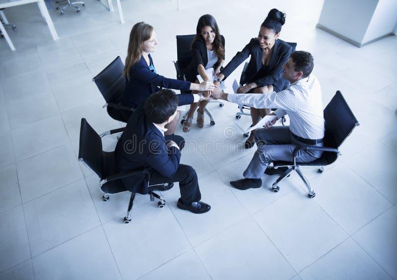 Gens d'affaires s'asseyant en cercle avec des mains encourageant ensemble photographie stock libre de droits