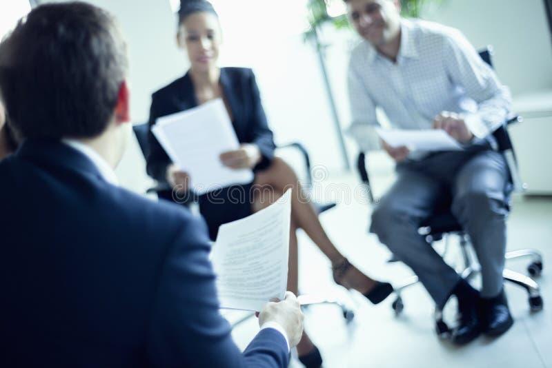 Gens d'affaires s'asseyant lors d'une réunion d'affaires, inclinaison photos libres de droits
