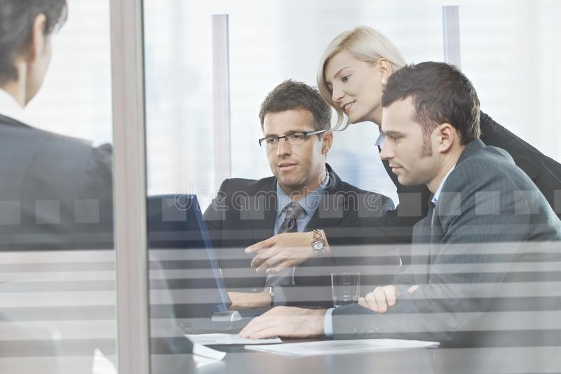 Gens d'affaires se réunissant dans la salle de réunion derrière le verre images stock