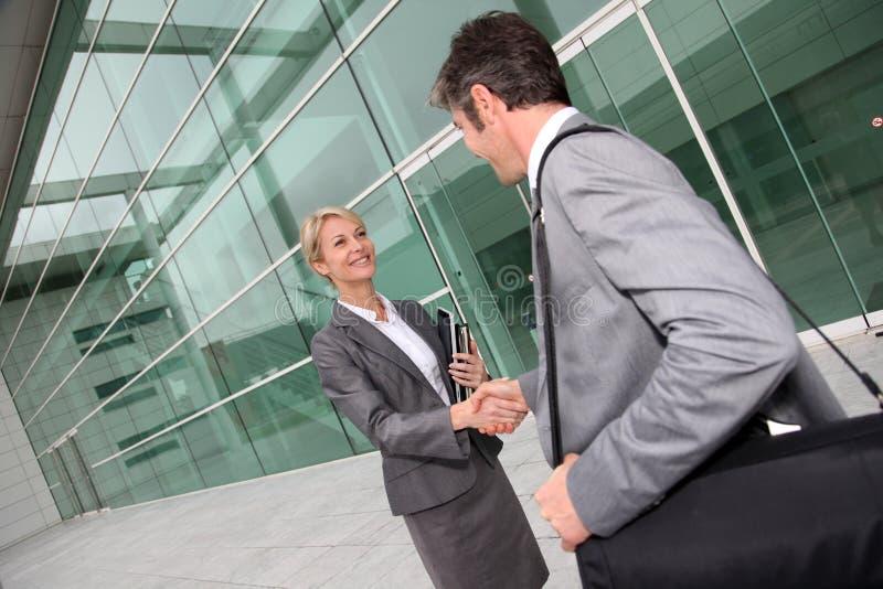 Gens d'affaires se réunissant devant l'immeuble de bureaux image stock