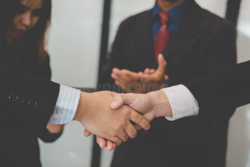 Gens d'affaires se serrant la main après avoir fini se réunissant  wor de Co photo libre de droits