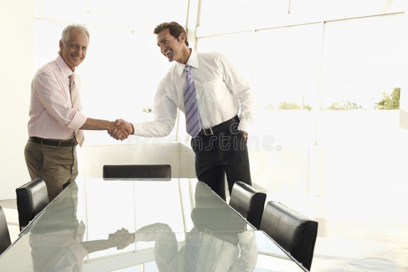 Gens d'affaires se serrant la main dans la salle de conférence image libre de droits