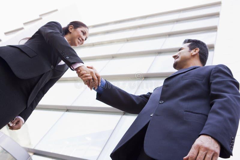 Gens d'affaires se serrant la main en dehors de bureau photo stock
