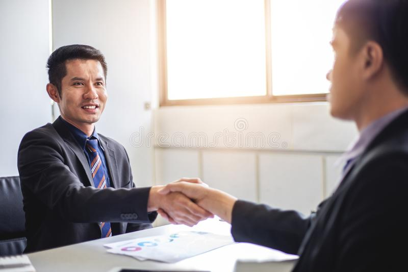 Gens d'affaires se serrant la main et souriant leur accord de signer le contrat et finissant une r?union image stock
