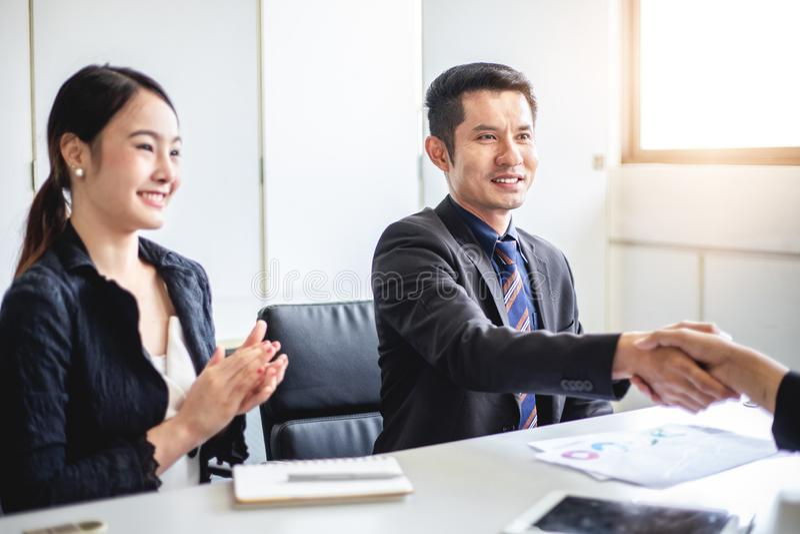 Gens d'affaires se serrant la main et souriant leur accord de signer le contrat et finissant une r?union image libre de droits