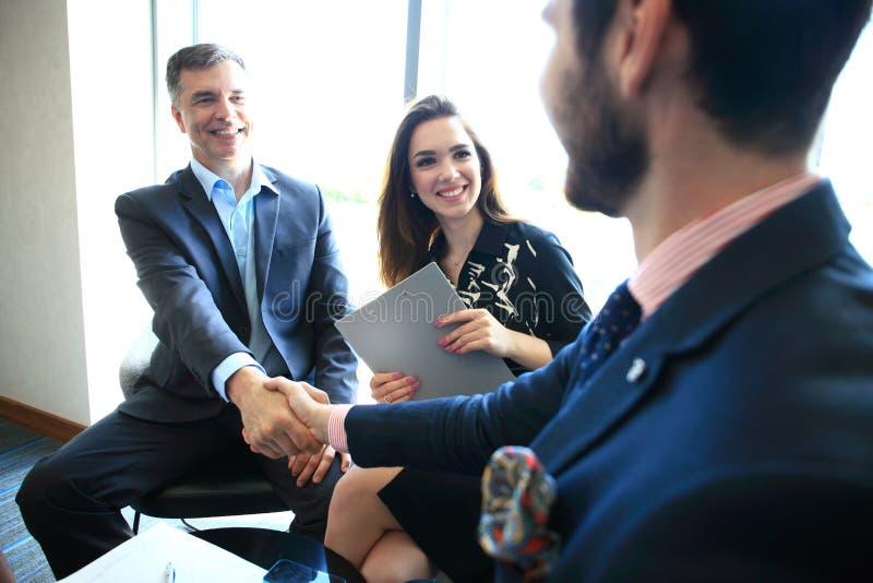 Gens d'affaires se serrant la main, finissant une réunion image stock