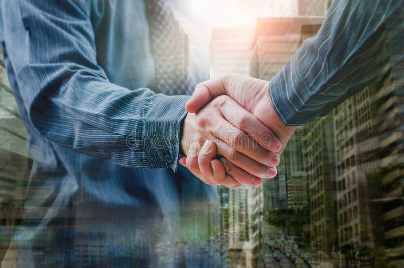 Gens d'affaires se serrant la main la double exposition image stock