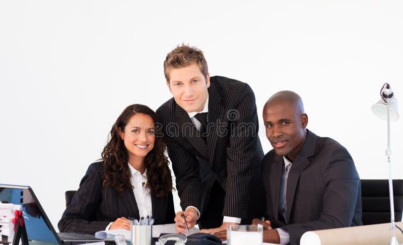 Gens d'affaires souriant à l'appareil-photo lors d'un contact photographie stock libre de droits