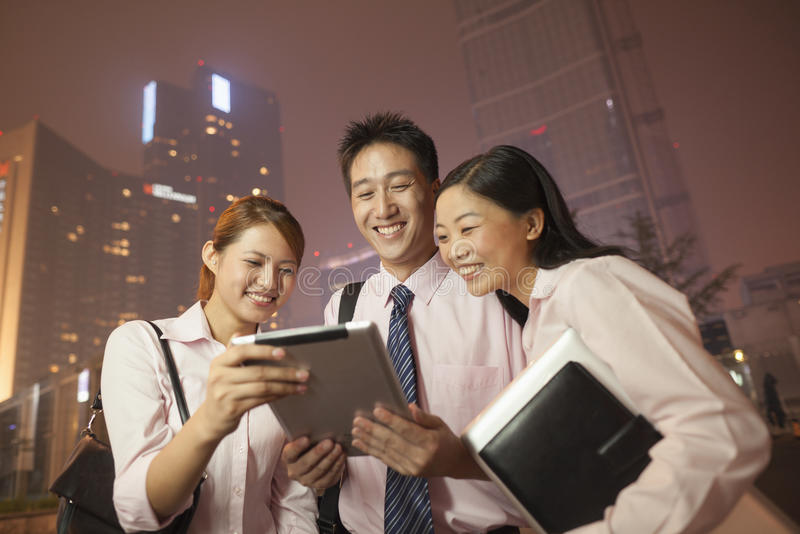 Gens d'affaires souriant et travaillant dehors la nuit image libre de droits