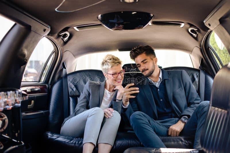 Gens d'affaires sur la banquette arrière de la limousine images libres de droits